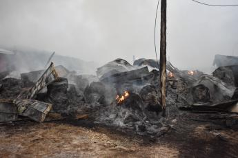Hundreds of bales of hay smolder hours after the initial spark sent this hay barn up in flames.  (Progress photo by Travis Dockery)