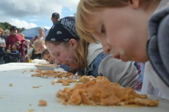 (Lorrie Ross• Clay County Progress) Daily pumpkin pie eating contests gather dozens of people to cheer on their favorite pie eaters. The competition sometimes gets fierce between siblings or friends eating pie side by side.