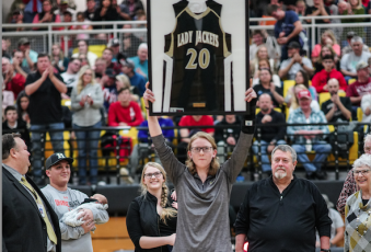 (Kelli Graves • Clay County Progress) Former Lady Yellow Jacket Amanda Thompson holds her now retired No. 20 high in front of a packed gym as her family looks on with smiles.