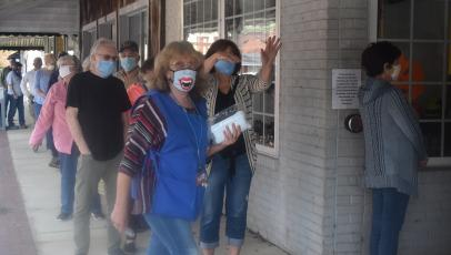 Clay County Election Board worker Linda Hagberg helps keep the line flowing during Thursday's opening day of One-Stop voting in Hayesville. Lines of mostly masked voters stretched to the end of the sidewalk most of the day, at times inching around the corner of Church and Main.