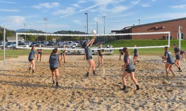 (Travis Dockery • Clay County Progress) The volleyball squads from Hayesville High School swarm the newly-finished outdoor court at the Clay County Recreation Center.