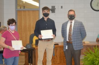 Hayesville High School students Michelle Pegues and Brady Shook tied for first place in the youth logo design contest held by People of Clay CARE. The students' logos were com- bined into one logo for the coalition. School Superintendent Dale Cole presented the students with their certificates and awards from the prevention coalition.