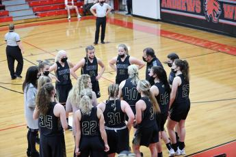 (Kelli Graves • Clay County Progress) Coach Chad McClure and his staff take advantage of a mask timeout to go over the game plan against the Lady Wildcats.