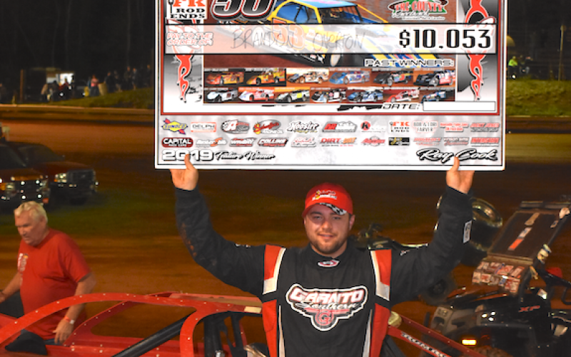 "(Travis Dockery • Clay County Progress) ""Big Sexy"" Brandon Overton proudly shows of his reward for winning the 16th Tarheel 50 at Tri County Racetrack."